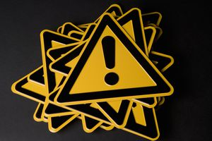 Stack of warning signs that are yellow triangles with exclamation marks on them