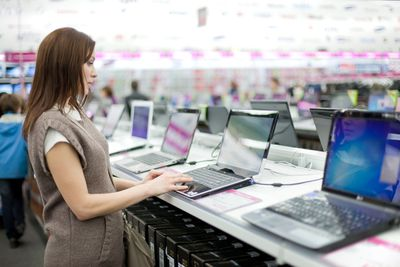 Woman browsing laptops in a store