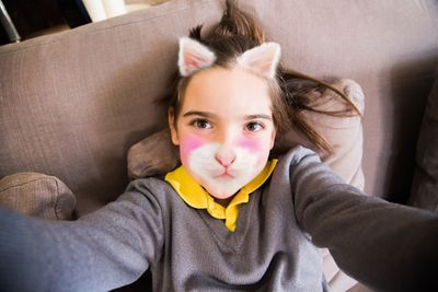 Little girl using Instagram app changing her face with kitten face