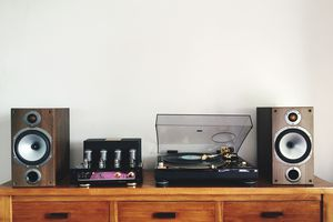 Turntable Amidst Speakers On Table By White Wall