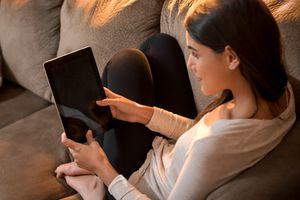 Woman sits on couch with tablet