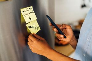 Person in the kitchen in the morning, posting sticky notes on the fridge