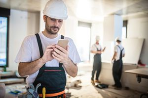 A construction worker using an iPhone.