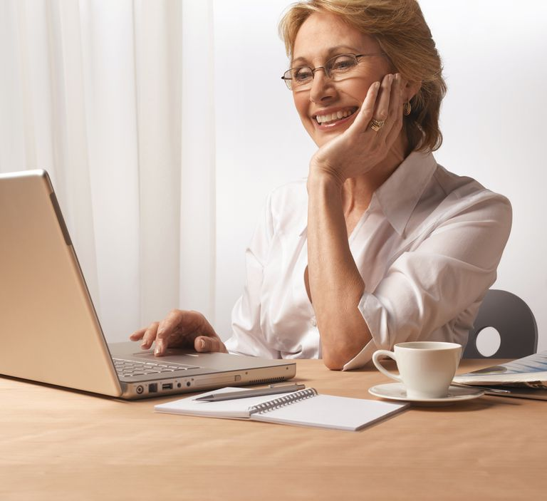 Woman chatting and reading mail on a laptop.
