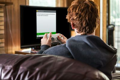 A teenager resetting his Xbox 360.