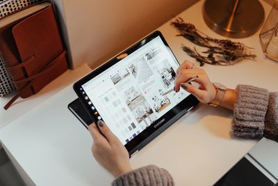 A photo of a person sitting at a desk and holding a stylus and a folded Samsung Chromebook tablet style computer.
