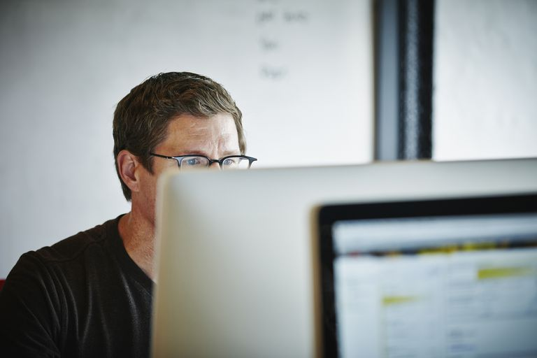 Man in glasses looking at mac desktop in an office