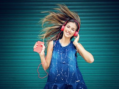 A young girl dancing to music while wearing red headphones plugged into a smartphone