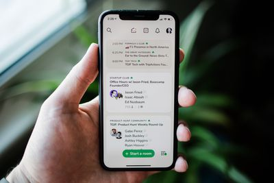 An iPhone XS in a hand with the Clubhouse social app open to the home screen.