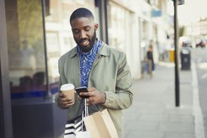 Young man on the street looking at a smarphone