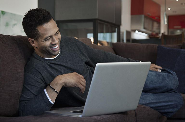 Mixed race man using laptop on sofa