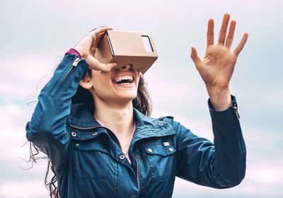 A woman wearing a Google Cardboard VR headset while using a virtual reality iPhone app.