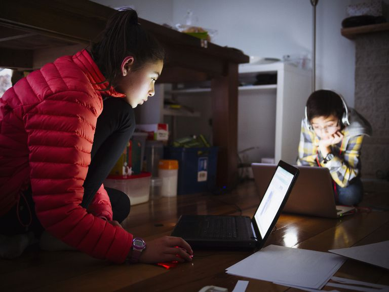 Two young siblings using laptops on floor