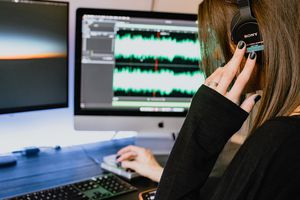 A person mixing audio on a computer.