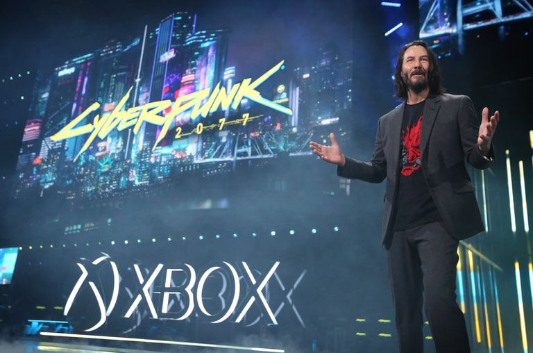 Keanu Reeves in front of a CyberPunk 2077 banner onstage at Xbox Event