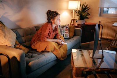 Woman on couch holding remote