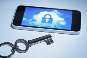 A cell phone displaying a padlock sits next to a big shiny silver key