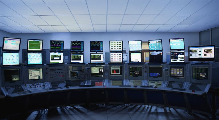 A photograph of a factory control room depicting 26 computer monitors showing various data and information.