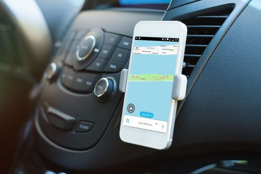 A car app displayed on a phone in a car dash mount.