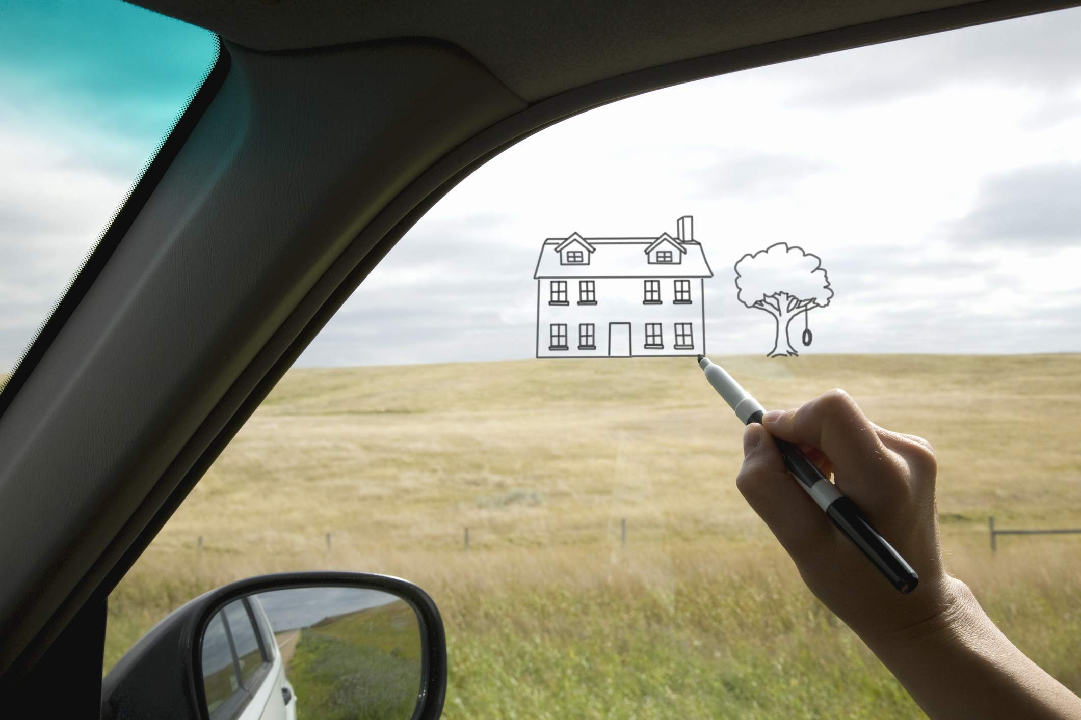 A person drawing a house on a car window