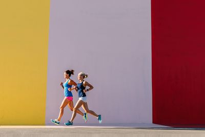 Women running against colorful wall
