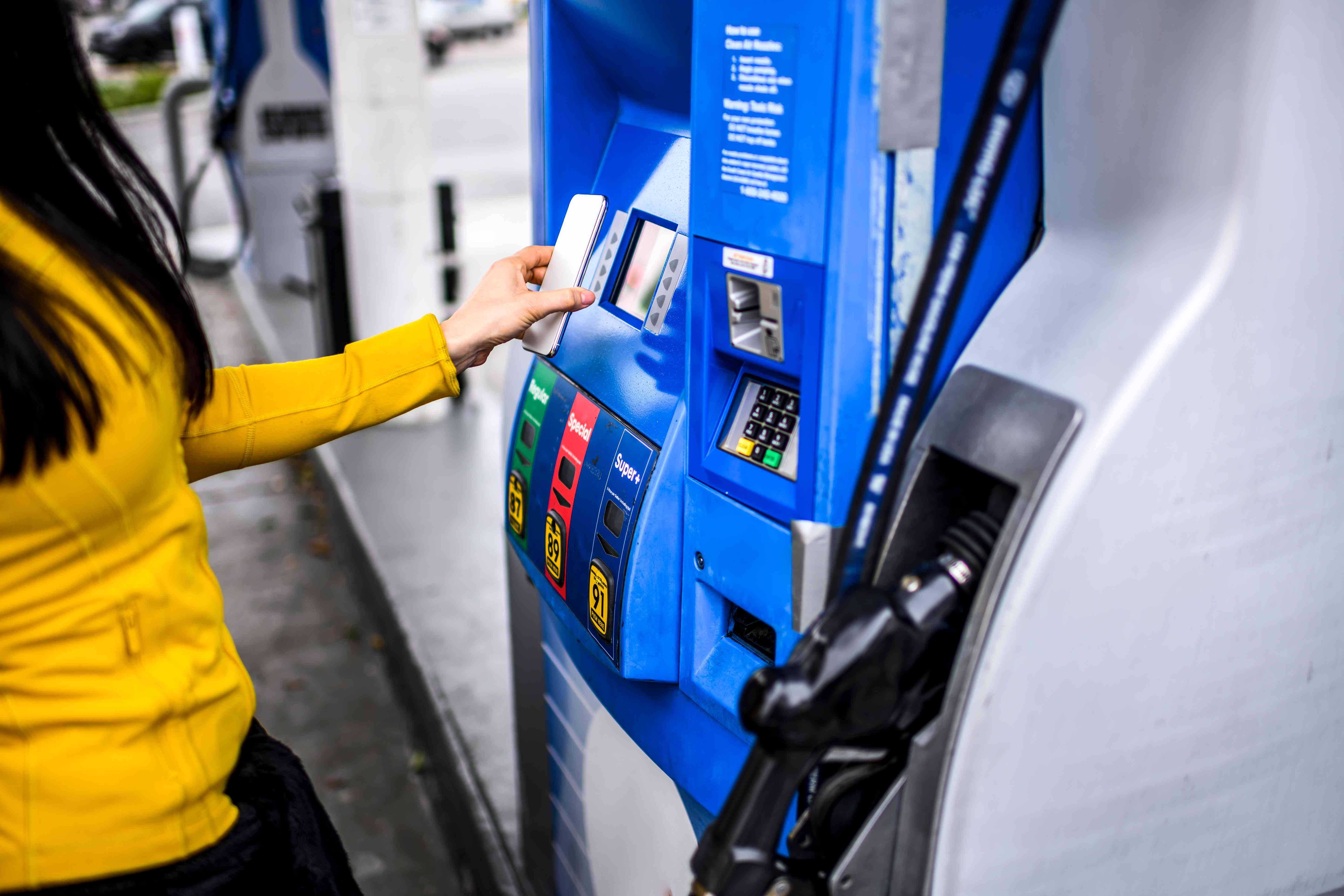 Making a contactless payment with a mobile phone at a gas station.