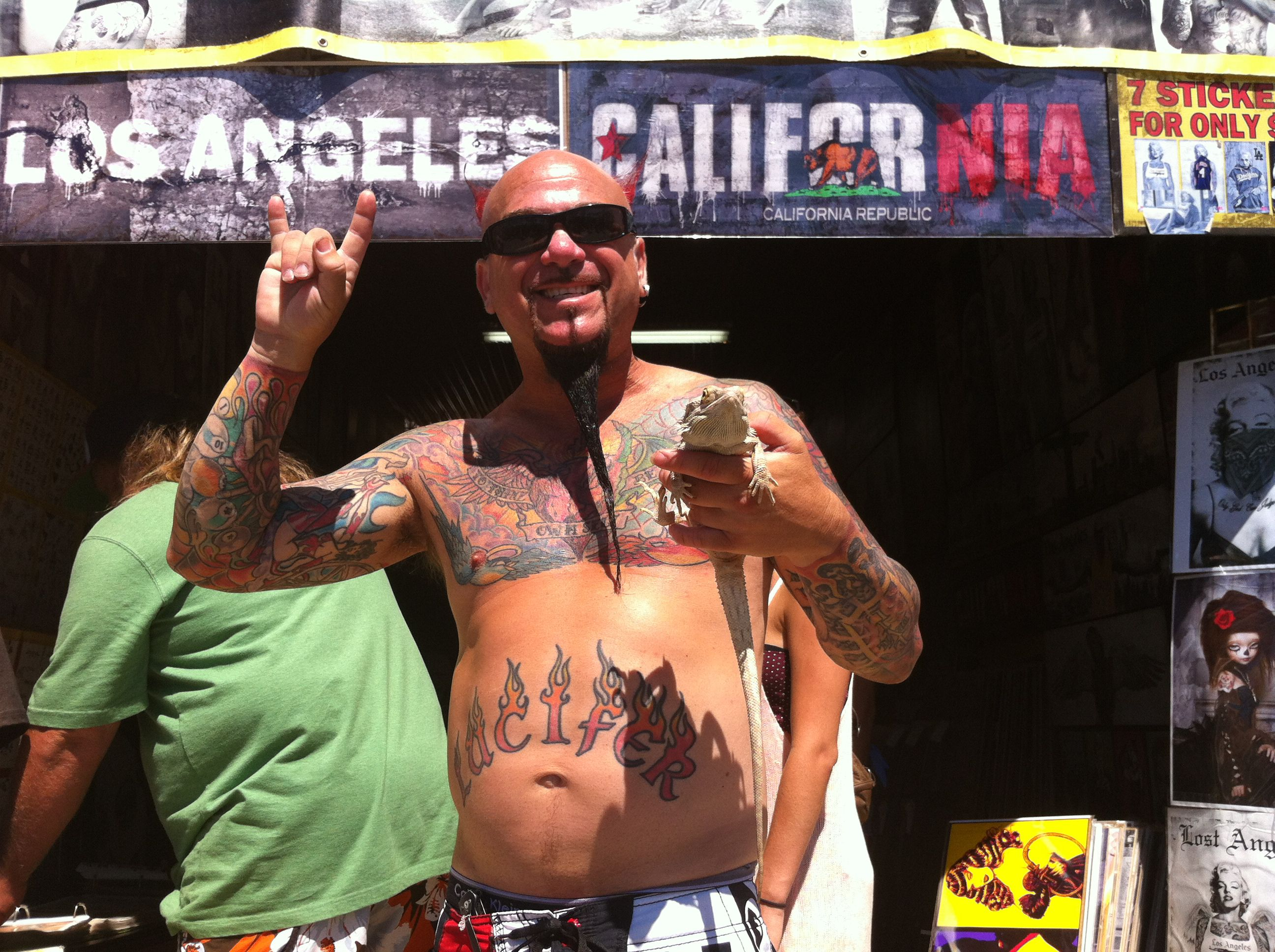 Tattooed man in front of LA banner holding lizard