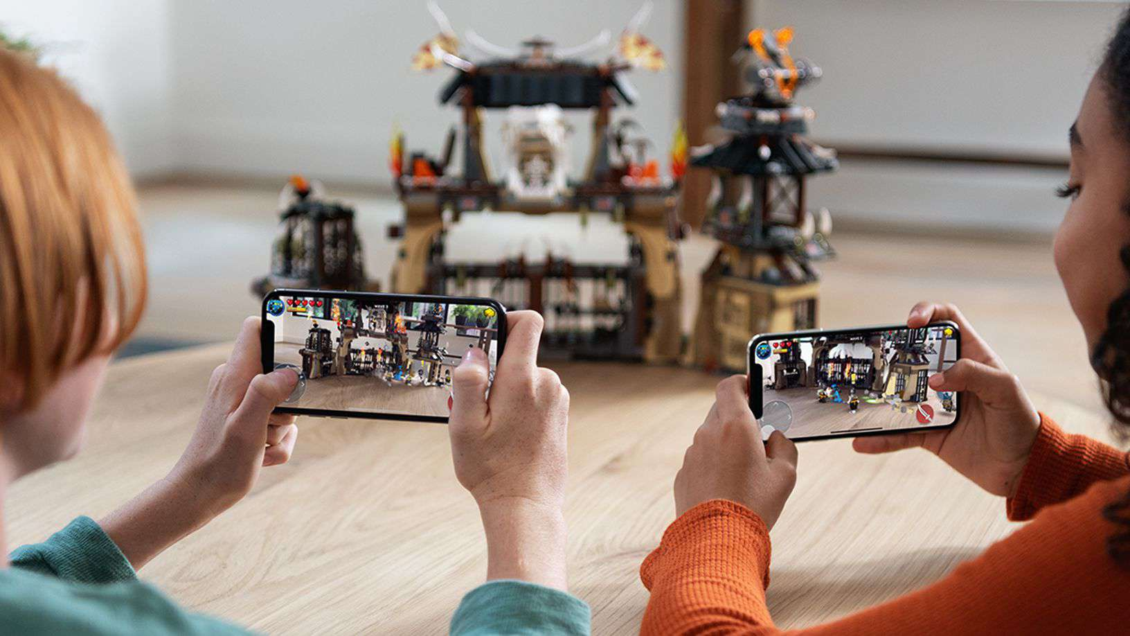 Children playing with augmented reality on iPhone with lego castle in the background