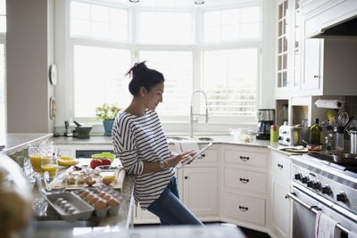 Blogger using an iPad in a kitchen while cooking