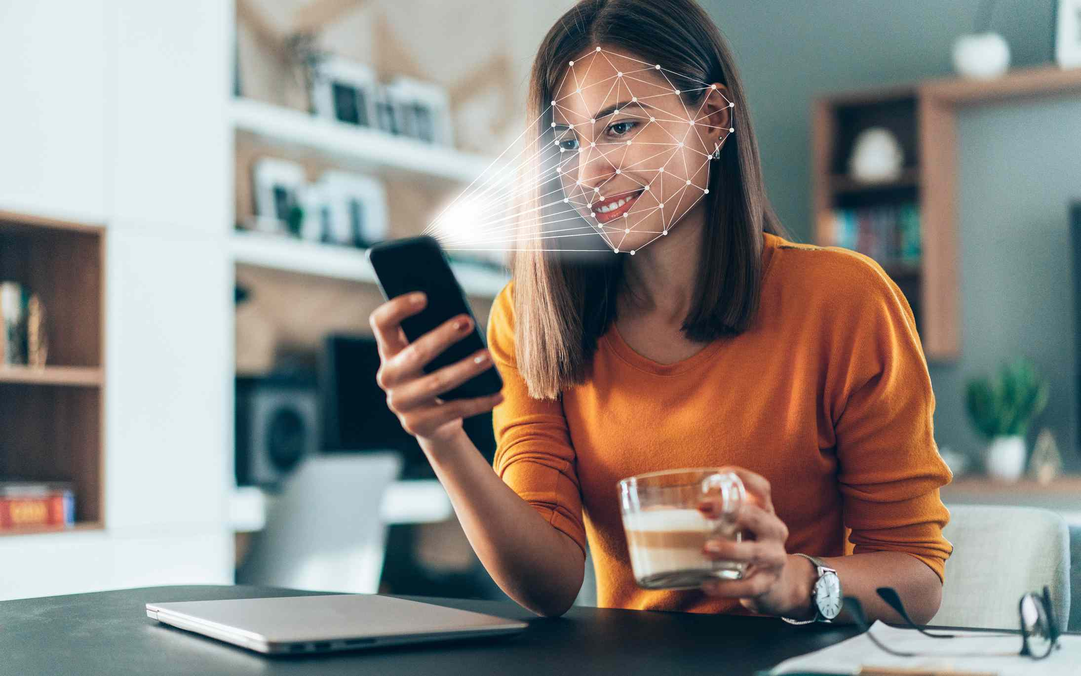 Someone using a biometric face scanner on a smartphone while sitting at a kitchen counter holding a cup of coffee.