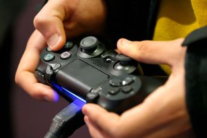Hands holding a PlayStation 4 controller