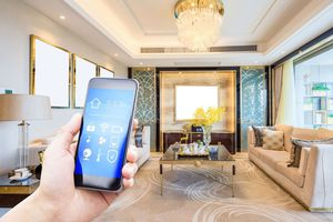 Hand holding smartphone with home control app in well lit living room