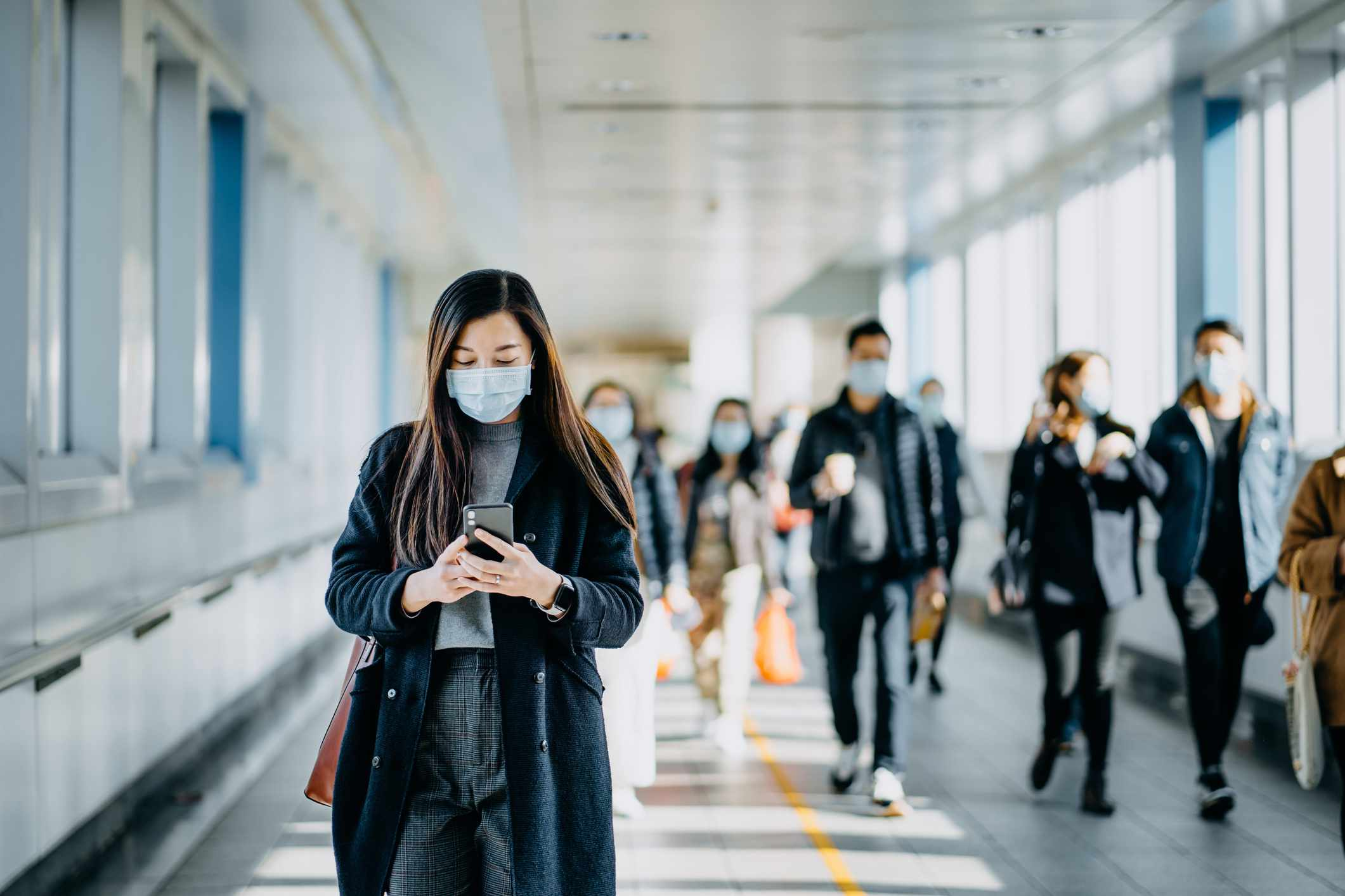 Woman checking phone with mask on