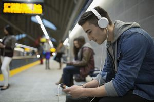 A person listening to a podcast while waiting for a train