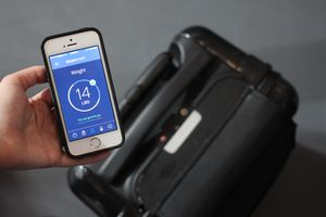 Hand holding a smartphone with luggage in the background