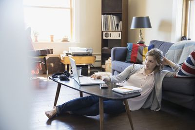 Woman Using Laptop on Living Room Floor