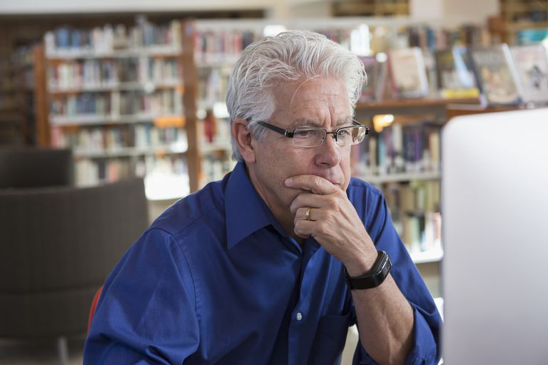 Pensive Hispanic man using computer in library