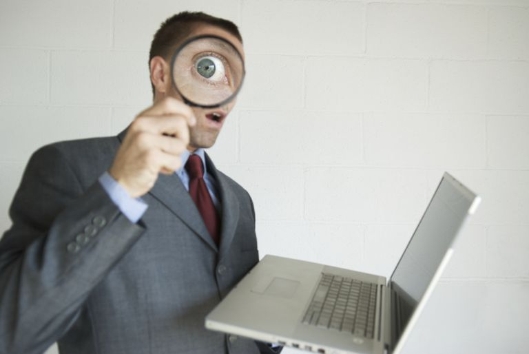 Businessman holding laptop holding magnifying glass up to his eye