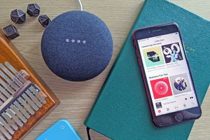 A Google Home speaker playing Apple Music with an iPhone nearby.