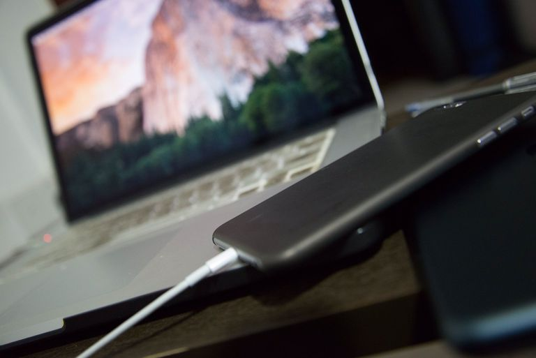 An iPhone is connected by USB to a Mac laptop.