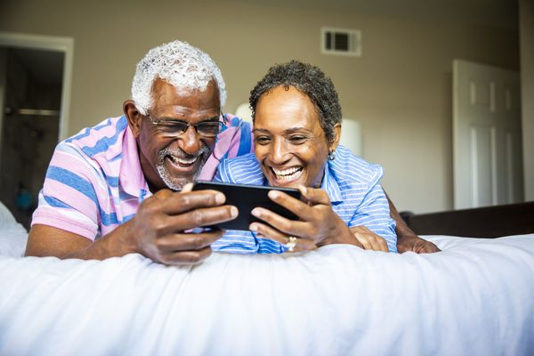 Two smiling older people watching something on their iPhone