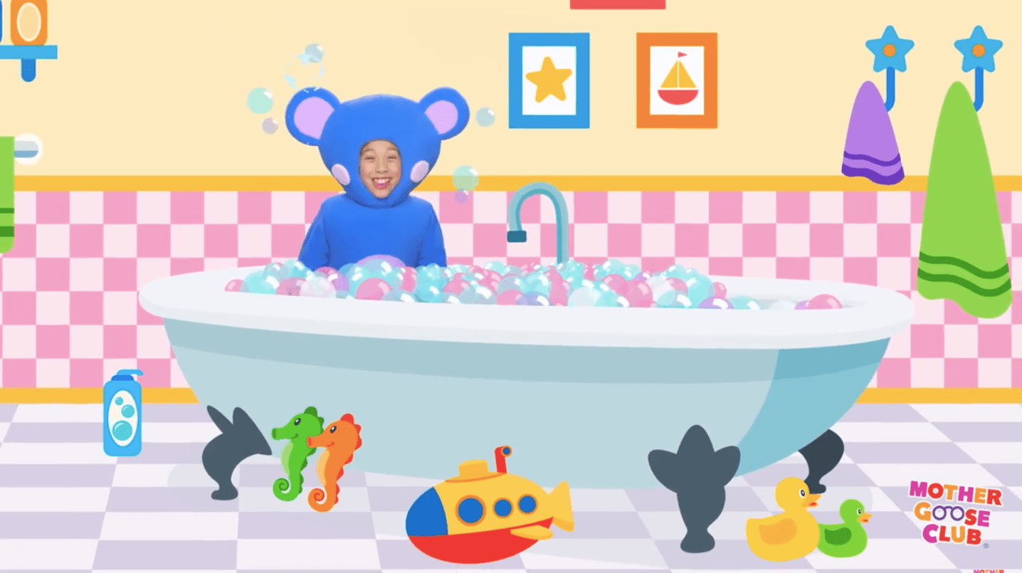 A blue mouse sits in a bathtub full of bubbles.