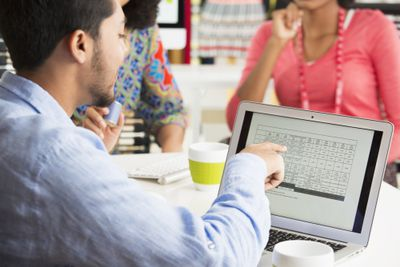 Man using spreadsheet on laptop with woman sitting across from him at the desk