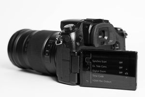A mirrorless Lumix camera showing the settings on the LCD display