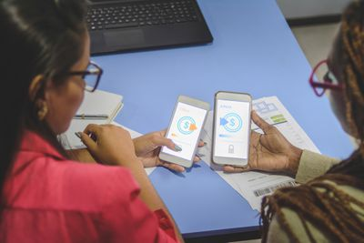 Two young people sending money through a money-sending app.