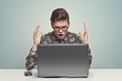A man looks exasperated at their laptop