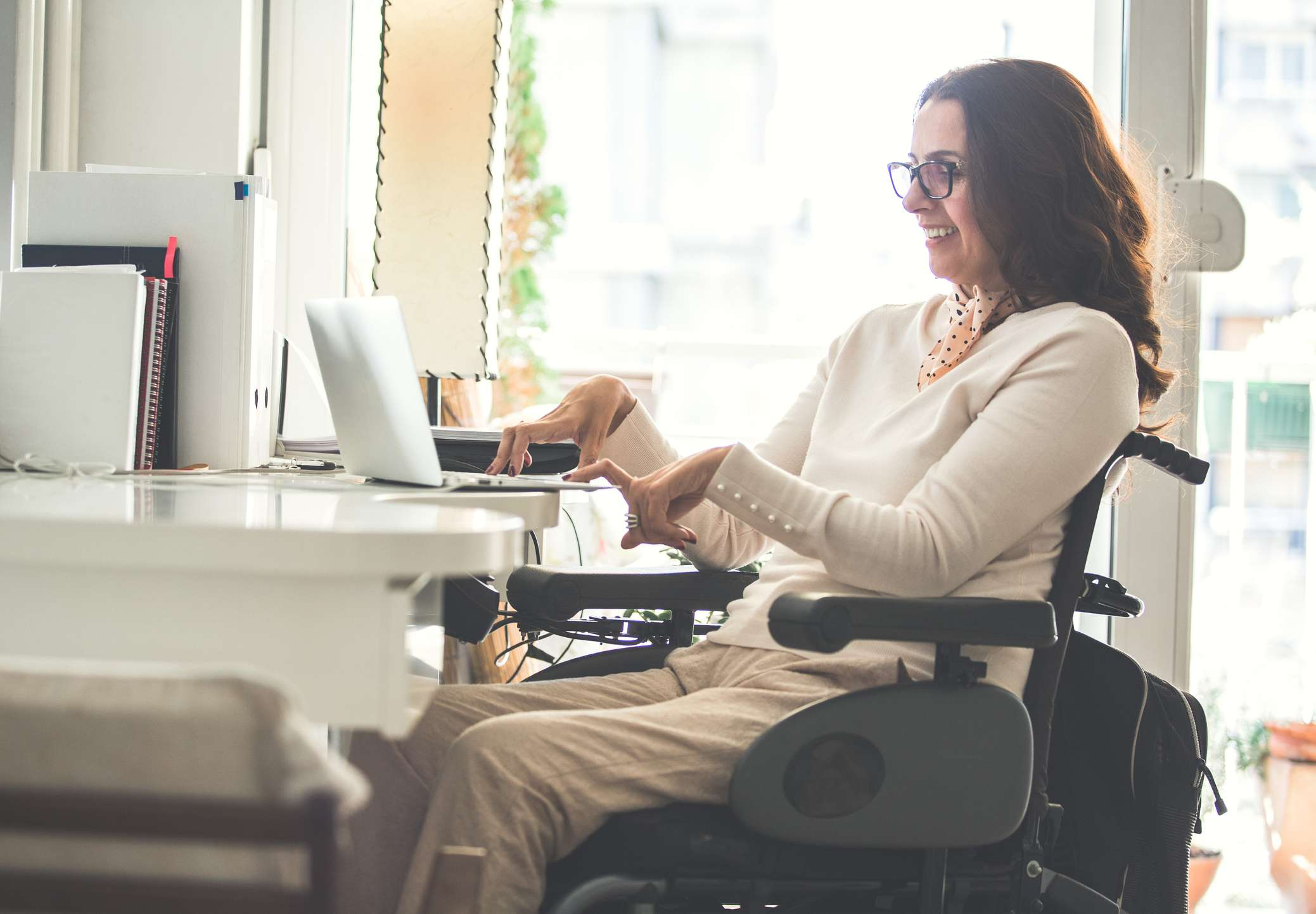 A person with disabilities working on a laptop computer in a home office.
