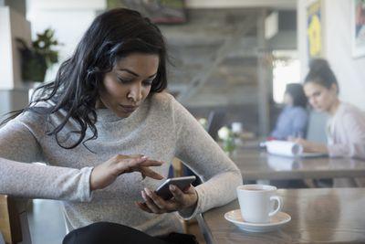 Woman in coffee shop using iPhone.