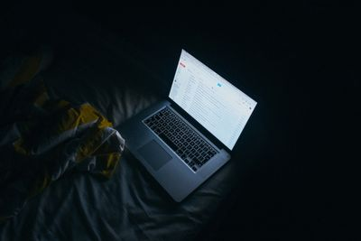 Laptop on bed with email open.