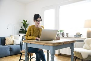 Woman using her Mac while sitting at a table in her living room.